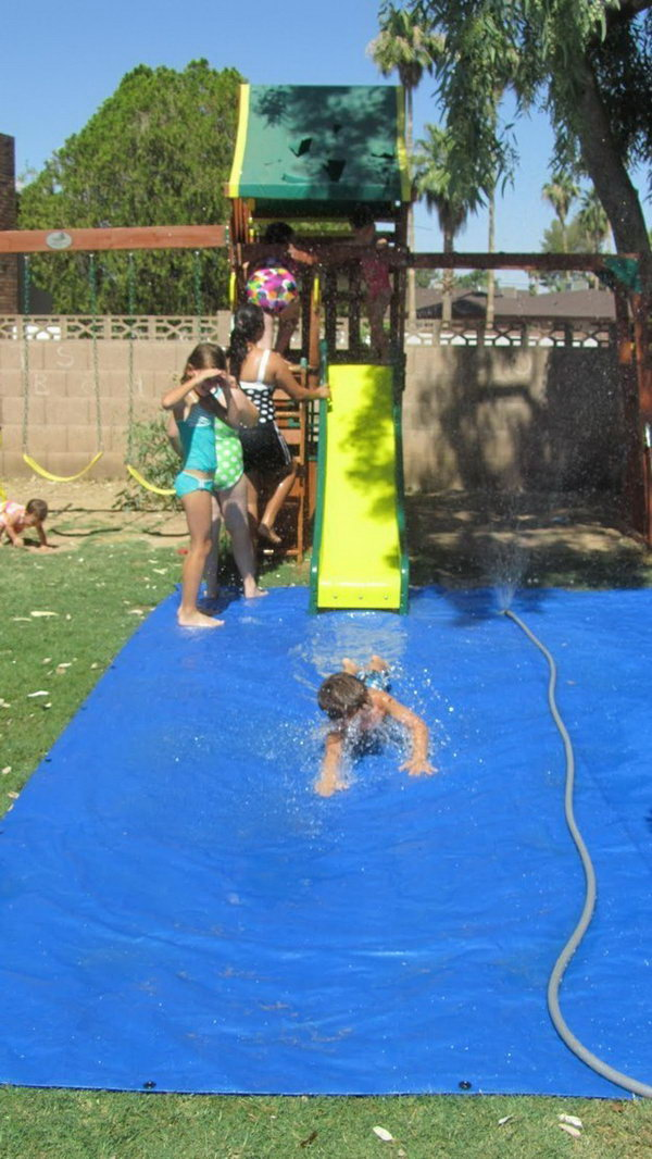 Use a tarp and sprinkler to create a fun splash pad for a slide