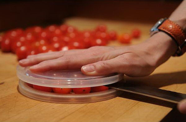 Cut small foods like cherry tomatoes by using two plastic lids. It'll save you time and protect you from any nasty cuts.