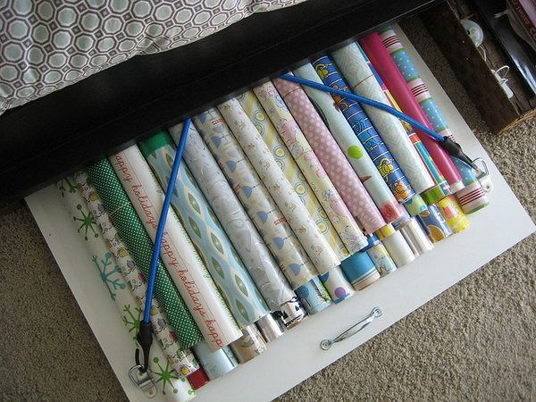 Bungee Cords Board for Wrapping Paper Storage Under the Bed. A board with bungee cords under your bed can be a great storage solution for the wrapping paper without dust. Keep it smooth and clean so you will not have to buy new gift wrap every time you wrap a present.