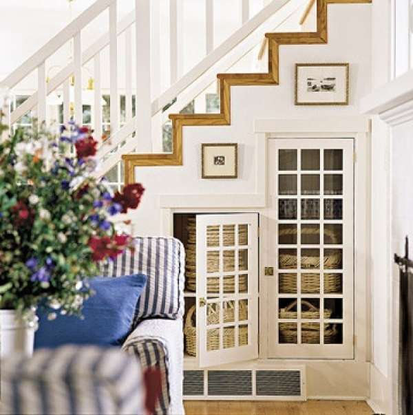 Mullioned glass pane doors add more elegance to this smart understair hideaway.  Baskets placed on the shelves are stylish storage  for your home.