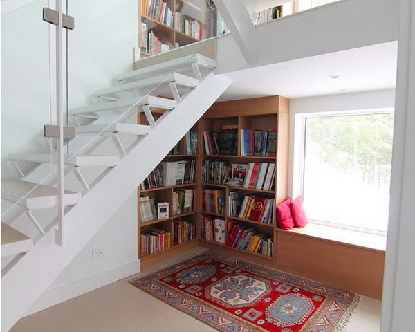 Create the open bookshelves under the stairs together with a reading nook besides the windows.