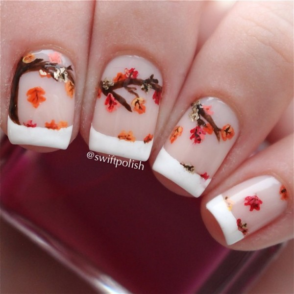 Fall Inspired French Manicure. French tip consisting of tree branches and falling leaves perfect for the fall season.