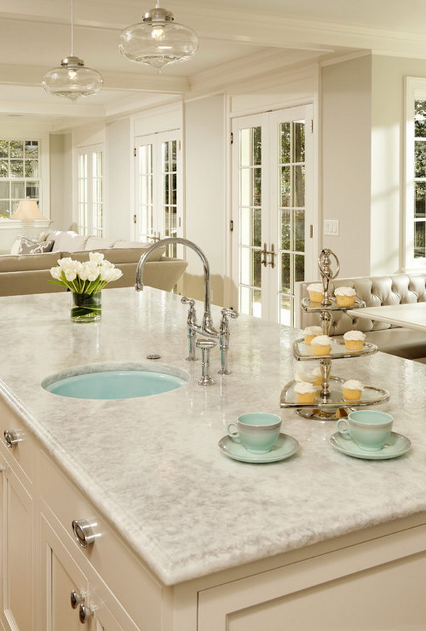White Princess Quartzite Countertop With White Cabinets And A Pop Of Green.