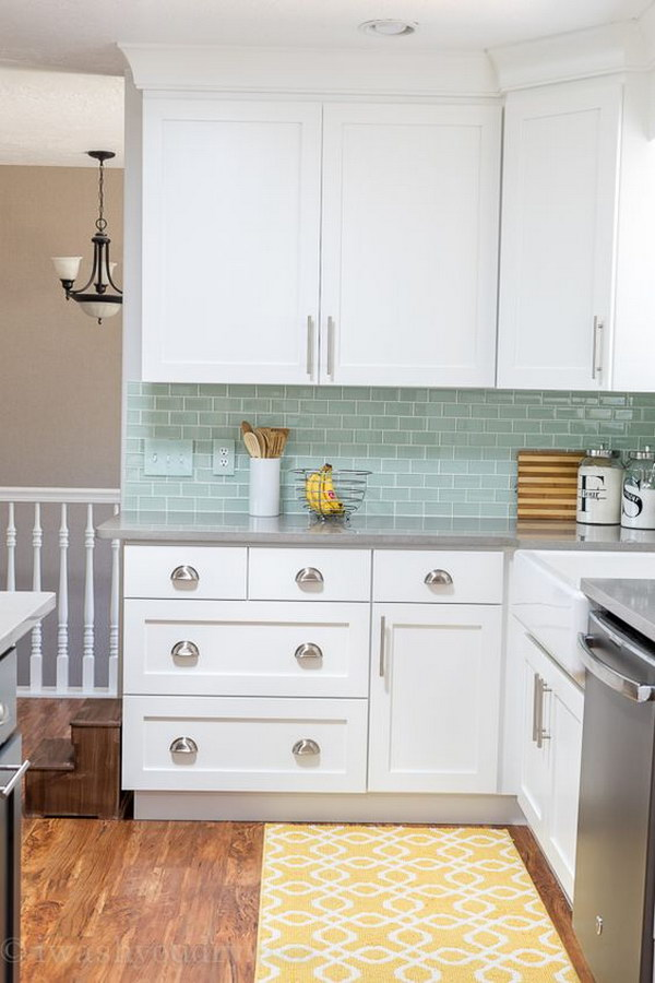 White Cabinets and Quartz Countertops That Look Like Concrete With Mint Backsplash Tiles.
