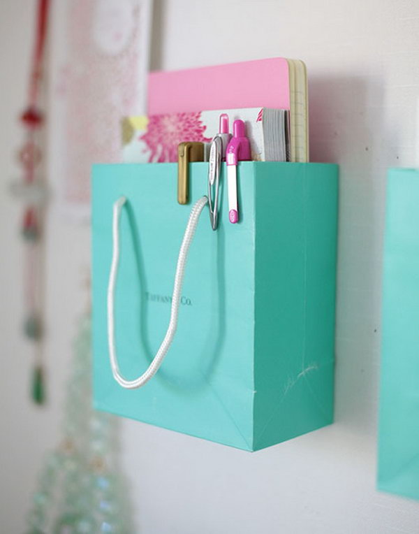 Shopping Bag Organization. Next time, don't throw away those really cute and really strong shopping bags.  You can actually repurpose them by mounting them on your wall and using them to store notebooks, magazines or other little office supplies.