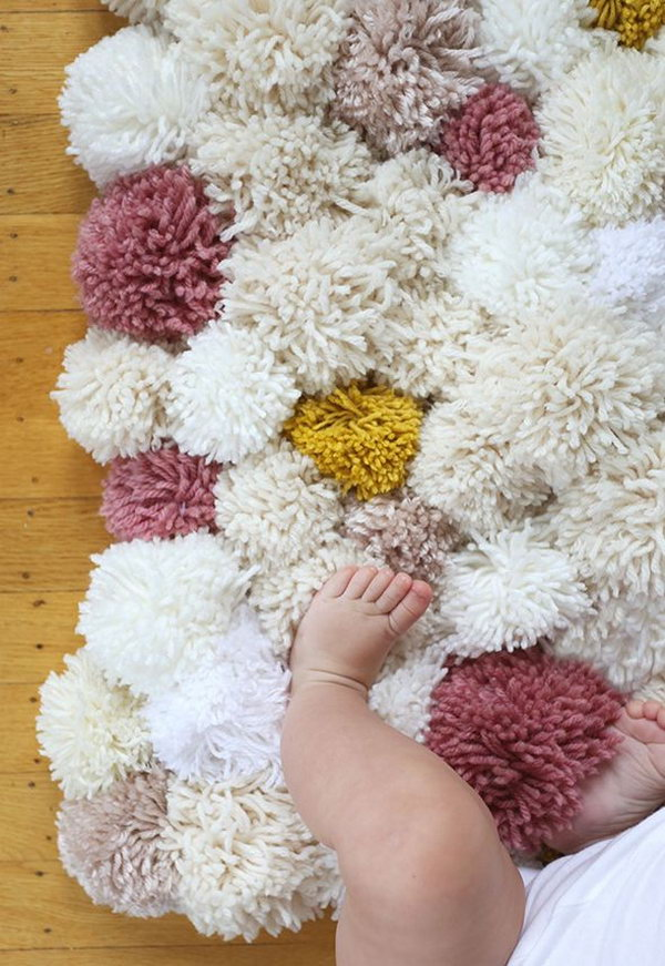 DIY Pom Pom Rug. You can't believe how easy it is to make this cute pom pom rug.