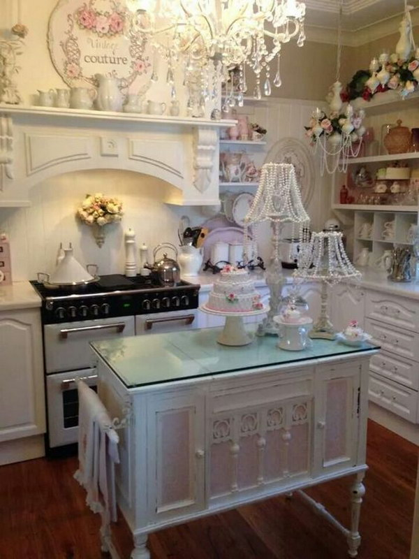 White Shabby Chic Kitchen with Small Pink Island and Beaded Lampshades.