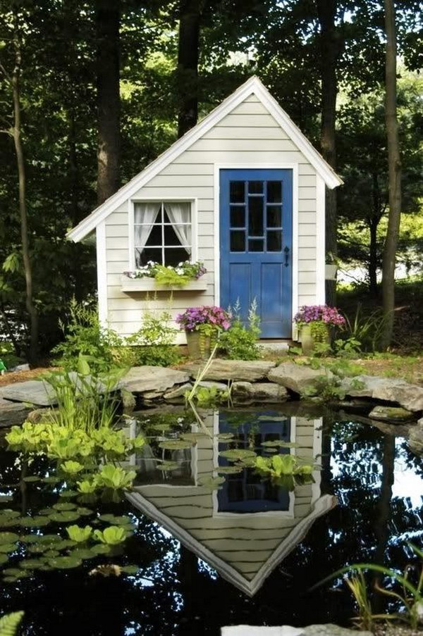 Small folly style cottage shed beside a lake.